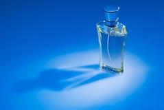 De fles van het parfum op blauwe achtergrond Royalty-vrije Stock Afbeelding