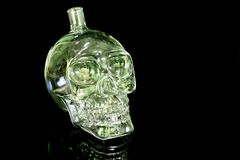 De fles van het schedelglas op de zwarte weerspiegelende oppervlakte Stock Afbeeldingen