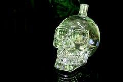 De fles van het schedelglas op de zwarte weerspiegelende oppervlakte Royalty-vrije Stock Afbeelding