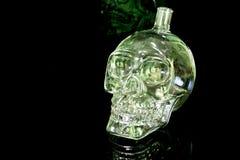 De fles van het schedelglas op de zwarte weerspiegelende oppervlakte Stock Afbeelding