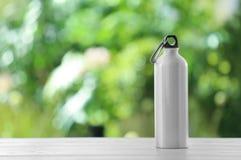 De fles van het sportenwater op lijst tegen vage achtergrond stock foto's