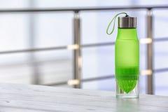 De fles van het sportenwater op lijst tegen vage achtergrond stock afbeeldingen