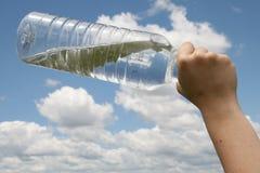 De fles van het water vóór bewolkte hemel Royalty-vrije Stock Foto's