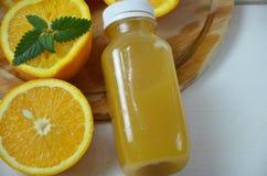 De fles van jus d'orangestudio schoot oranje organisch vers gedrukt sap in een kleine plastic fles op kleurrijk stock foto's