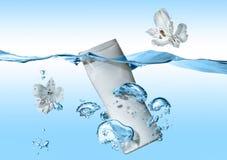 De fles van kosmetische melk, kosmetische room, kosmetisch water in de blauwe watergolf met plons en grote luchtbellen dichtbij b Royalty-vrije Stock Afbeelding