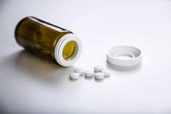 De fles van pillen met een deksel, sluit omhoog Royalty-vrije Stock Foto's
