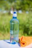 De fles van water en handdoek Stock Foto