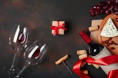 De fles wijn, giftdoos, blauwe stinky kaas, rode druiven, amandelen, kurketrekker en kurkt, op roestige hoogste mening als achter stock afbeeldingen