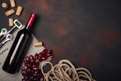 De fles wijn, rode druiven, kurketrekker en kurkt, op roestige hoogste mening als achtergrond royalty-vrije stock foto's