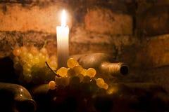 De flessen en de druiven van de wijn met kaars Stock Afbeeldingen