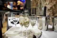 De flessen en de glazen van Champagne Stock Foto's