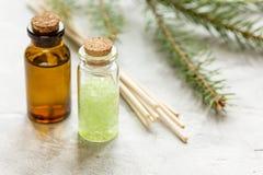 De flessen etherische olie en spar vertakt zich voor aromatherapy en kuuroord op witte lijstachtergrond royalty-vrije stock fotografie
