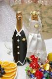 De flessen van Champagne in huwelijkskleren Stock Afbeeldingen