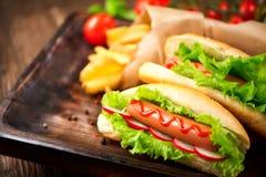 De flessen van de ketchup en van de mosterd op achtergrond Geroosterde hotdogs met ketchup Royalty-vrije Stock Foto