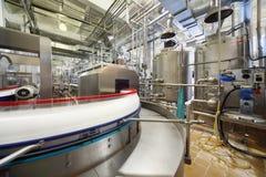 De flessen van de melk bewegen zich door lange pijpleiding Stock Afbeelding
