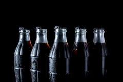 De flessen van het sodaglas status op een rij geïsoleerd op een zwarte Stock Fotografie