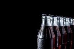 De flessen van het sodaglas status op een rij geïsoleerd op een zwarte Stock Foto