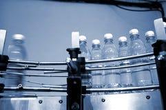 De flessen van het water op transportband Royalty-vrije Stock Fotografie
