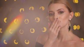 De flirtvrouw maakt luchtkus op een camera, langzame motie, gele bokehachtergrond stock video
