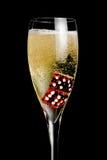 De fluit van Champagne met gouden bellen en het rood dobbelen Stock Foto's