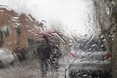 De focused image of rain falling on the road, looking out the window. Blurry car silhouette. Rain drops on window, rainy weather Royalty Free Stock Photography