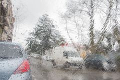 De focused image of rain falling on the road, looking out the window. Blurry car silhouette. Rain drops on window, rainy weather Stock Images