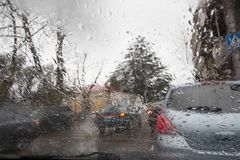 De focused image of rain falling on the road, looking out the window. Blurry car silhouette. Rain drops on window, rainy weather Royalty Free Stock Images