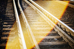 De focused railroad track. De focused curved railroad tracks with a lens flare. May be used as travel background Royalty Free Stock Photography