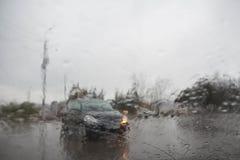 De fokuserade bilden av regn som faller på vägen som ut ser fönstret Royaltyfri Bild