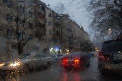 De fokuserade bilden av regn som faller på vägen som ut ser fönstret Arkivfoto