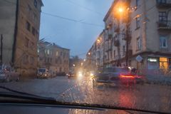 De fokuserade bilden av regn som faller på vägen som ut ser fönstret Oskarp bilkontur Royaltyfri Fotografi