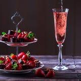 De fonkelende roze wijn wordt gegoten in glas Tribune met aardbeien stock foto