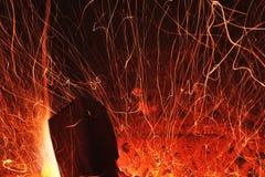 De fonkelingen van de brand met logboekhout Stock Afbeeldingen
