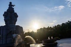 De fontein, de jongenszitting op bal en het spelen de fluit, water ontsnappen van boomstammenolifanten Stock Foto