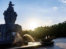 De fontein, de jongenszitting op bal en het spelen de fluit, water ontsnappen van boomstammenolifanten Stock Foto's