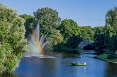 De fontein met een regenboog en een achtergrond Stock Foto's