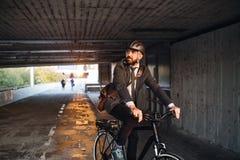 De forens van de Hipsterzakenman met elektrische fiets die naar het werk in stad reizen stock fotografie