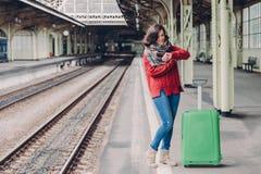 De foto van aantrekkelijke jonge vrouw wacht trein bij station, gekleed in gebreide sweater en de jeans, tribunes dichtbij groene royalty-vrije stock foto