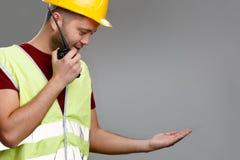 De foto van bouwer in helm met walkie-talkie in van hem dient geel vest met opgeheven omhoog palm in stock foto's