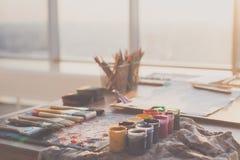 De foto van de hoekmening van palet met gemengde die olieverven, gouache, kleurpotloden en penselen in kunststudio worden geplaat Royalty-vrije Stock Fotografie