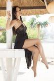 De foto van de voorraad van mooie lange donkerbruine vrouw op het strand in Stock Afbeeldingen