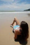 De foto van de voorraad van mooie lange donkerbruine vrouw op het strand in Royalty-vrije Stock Foto
