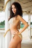De foto van de voorraad van mooie lange donkerbruine vrouw op het strand in Stock Foto