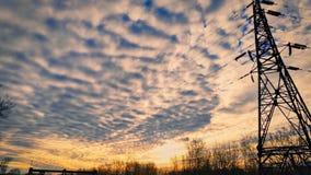 De foto van een mooie fabelachtige ochtendhemel met cirrus betrekt tegen de het toenemen zon van bomen en de lijnen van de machts stock afbeelding