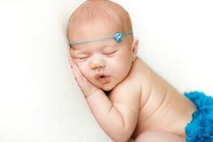 De foto van een pasgeboren baby krulde omhoog het slapen op een deken Stock Fotografie