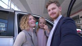 De foto van familieselfi in autowinkel, grappig paar met leuk jong geitjemeisje met sleutels fotografeerde op smartphone dichtbij stock videobeelden