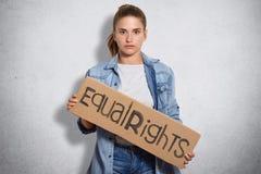 De foto van feministe in denimjasje, houdt teken de geschreven Gelijke rechten, die de vrouwen rechten en macht hebben, isoated o royalty-vrije stock fotografie