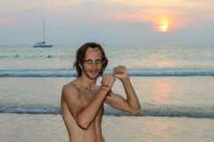 De foto van het kleurenportret van de knappe mens die omhooggaand en tijdens de zonsondergang bij het strand glimlachen kijken Stock Afbeeldingen