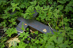 De foto van het zwarte steen Christelijke kruis die in het groene gras liggen stock foto's