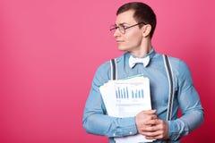 De foto van de jonge knappe mens die in bureau werken, draagt blauw overhemd, die zich met documenten op roze achtergrond in foto royalty-vrije stock fotografie